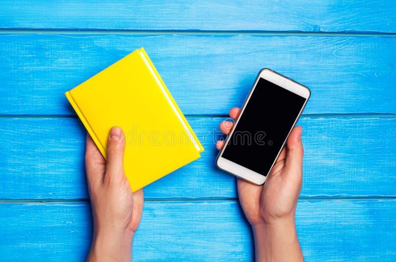 一个人拿着一本黄皮书和一个电话在蓝色木背景 在研究和电话之间的选择 电话瘾 免版税库存图片