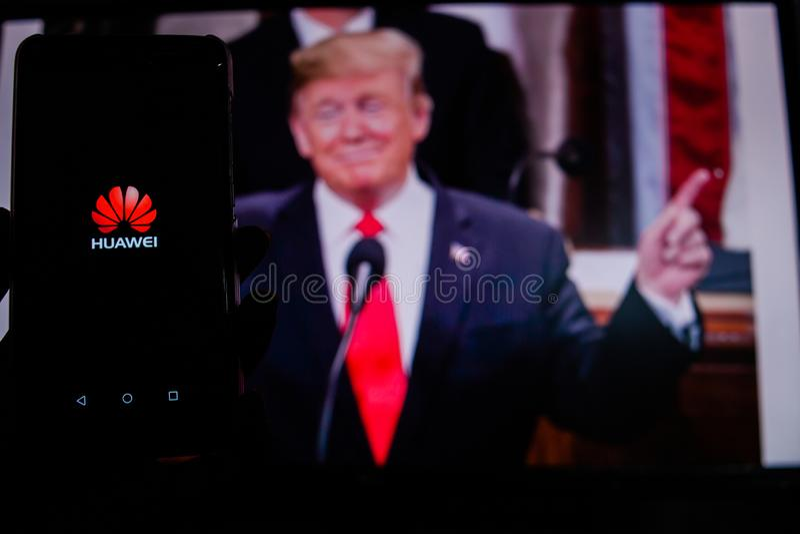 一个人拿着显示谷歌戏剧商店的商标在唐纳德・川普前面的图片的一个机器人智能手机 免版税库存照片