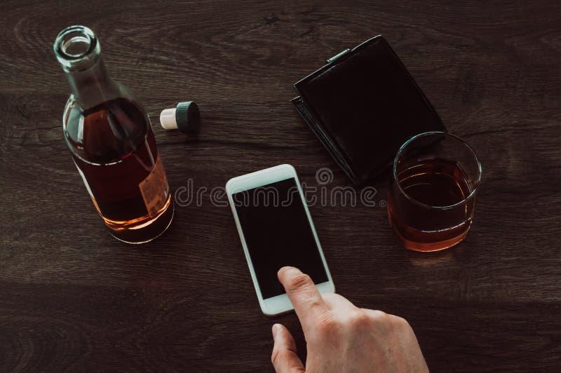 一个人按在一个手机的一个手指 其次在桌一杯威士忌酒、一个瓶威士忌酒和钱包 库存图片