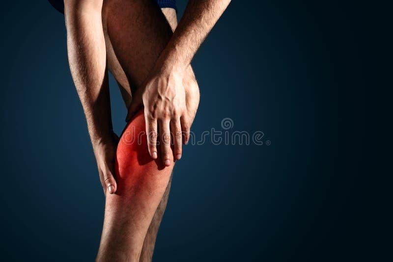 一个人握伤害的一条腿,黑暗的背景的,特写镜头,在红色表明的痛苦一个人 库存图片