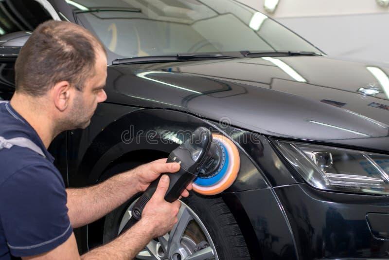 一个人擦亮一辆黑汽车 库存图片