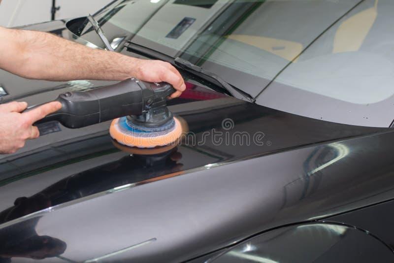 一个人擦亮一辆黑汽车 免版税库存照片