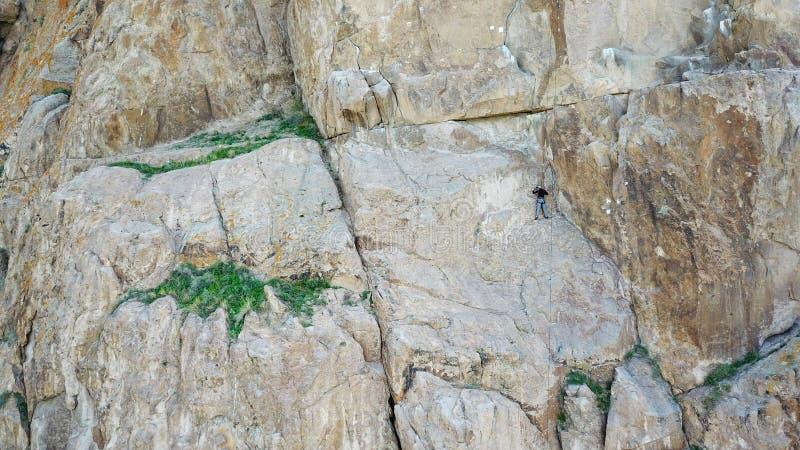 一个人攀登峭壁 活跃休闲和体育 爬上岩石 库存图片