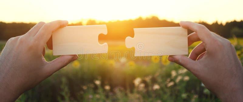 一个人收集收集木难题在日落 成功,企业解答的概念 战略和目标成就 ? 免版税库存照片