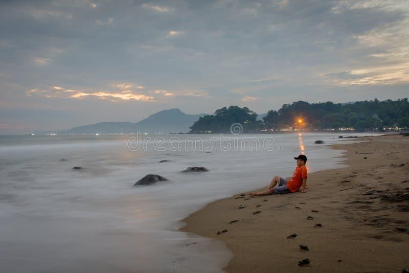 一个人是和享受片刻坐卡朗火山Hawu海滩,西爪哇省,印度尼西亚 库存照片