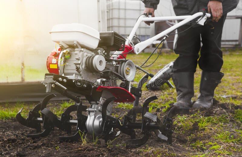 一个人是犁土地的农夫在有手拖拉机耕地机的庭院里 在犁领域的农业劳动 免版税库存照片