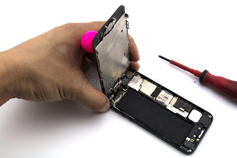 一个人是他准备修理手机变动屏幕和盒的安装工 图库摄影