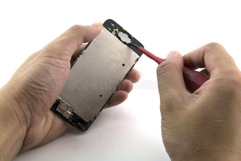 一个人是他准备修理手机变动按钮家庭屏幕的安装工 库存图片