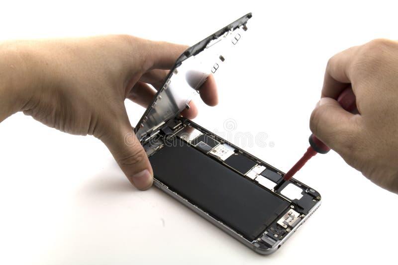 一个人是他准备对手机修理他是变动手机电池的安装工 库存图片