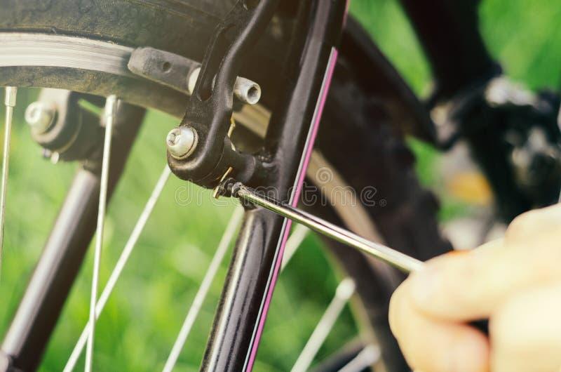 一个人松开有一把螺丝刀的螺栓在一个登山车的登上轮式制动器在草背景的  库存图片