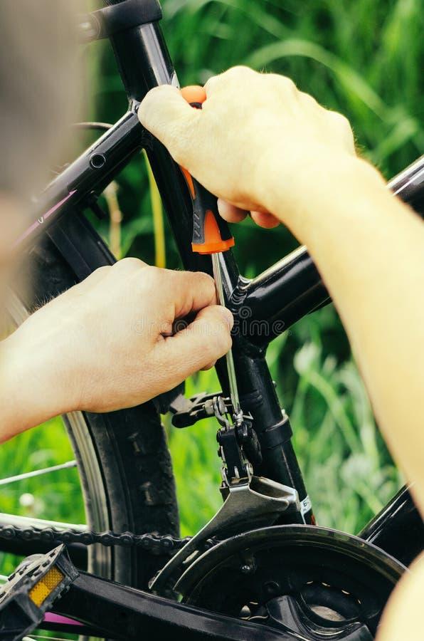 一个人松开有橙色螺丝刀的螺栓在草背景的一个登山车链子  在的修理 图库摄影