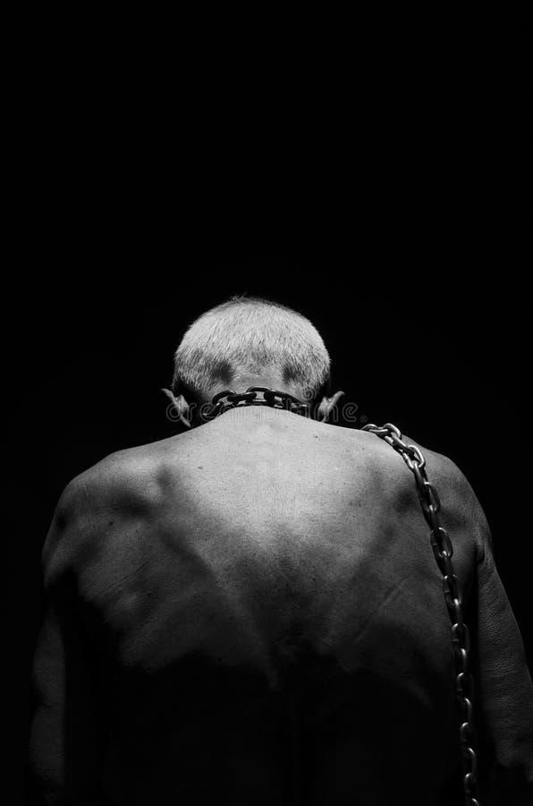奴隶制 一个人栓与在他的脖子的一个链子 库存照片
