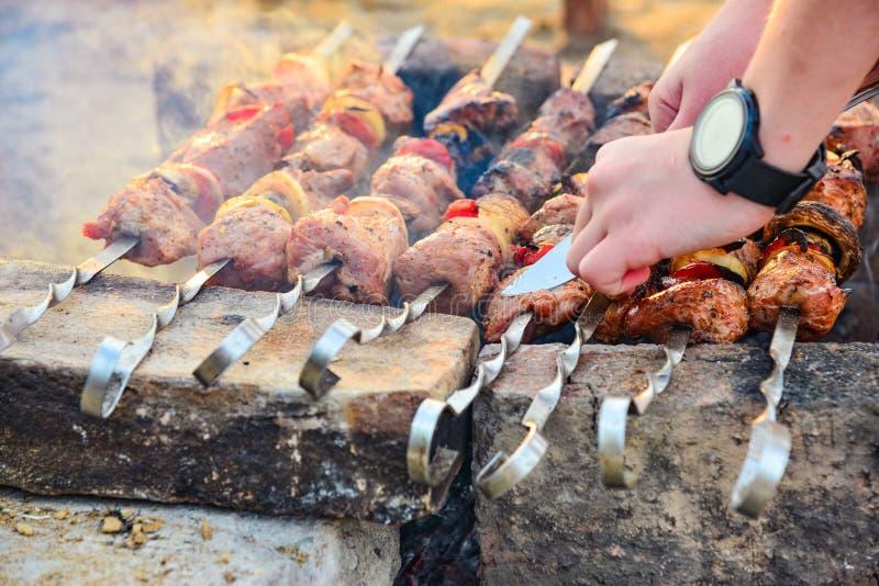 一个人油煎在串的烤肉串并且切除了与刀子的肉,烤肉用葱,蘑菇和肉 免版税图库摄影