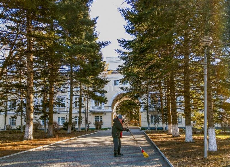 一个人清扫道路对与笤帚的疗养院大厦 免版税库存照片