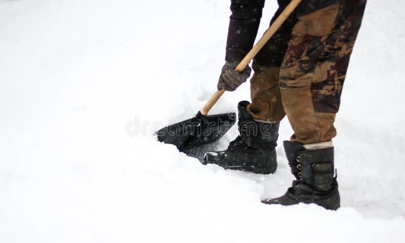 一个人清洗雪与铁锹 雪打扫灰尘  关闭 库存图片