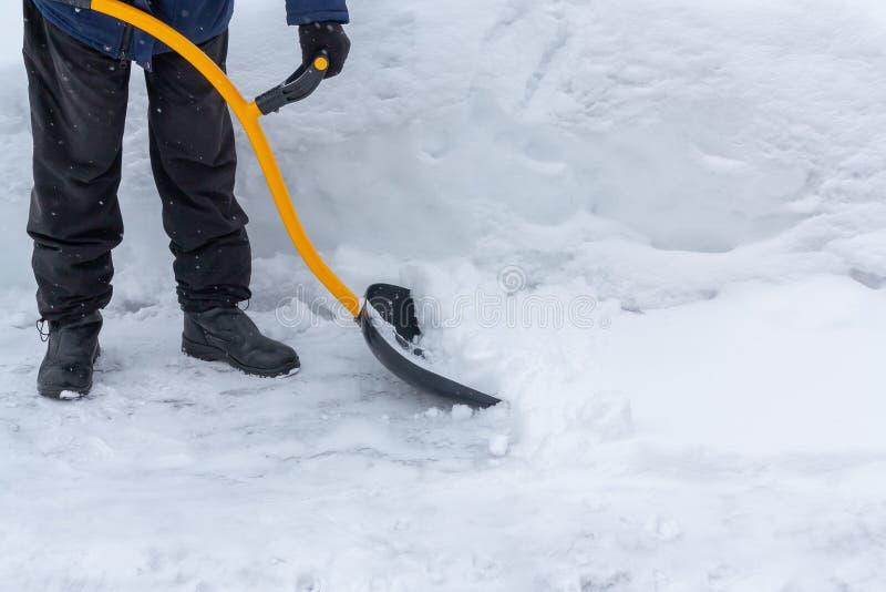 一个人清洗雪在围场与铁锹在以后大雪 免版税库存照片