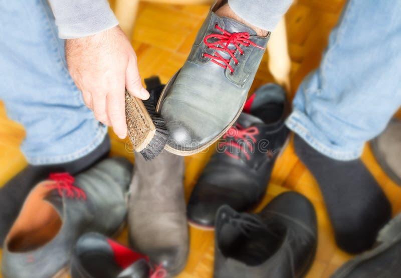 一个人清洗鞋子与刷子 图库摄影