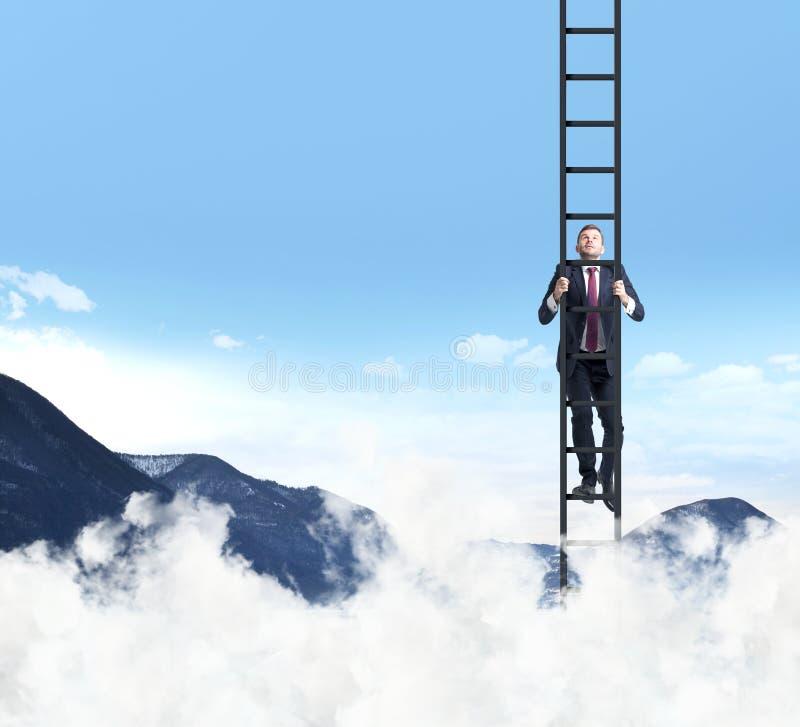 一个人爬上梯子 云彩和山风景 免版税库存照片