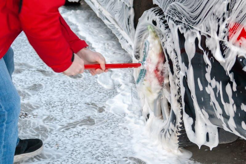 一个人用在自助洗车的泡沫摩擦倾吐的一辆黑汽车的轮子与刷子 库存照片