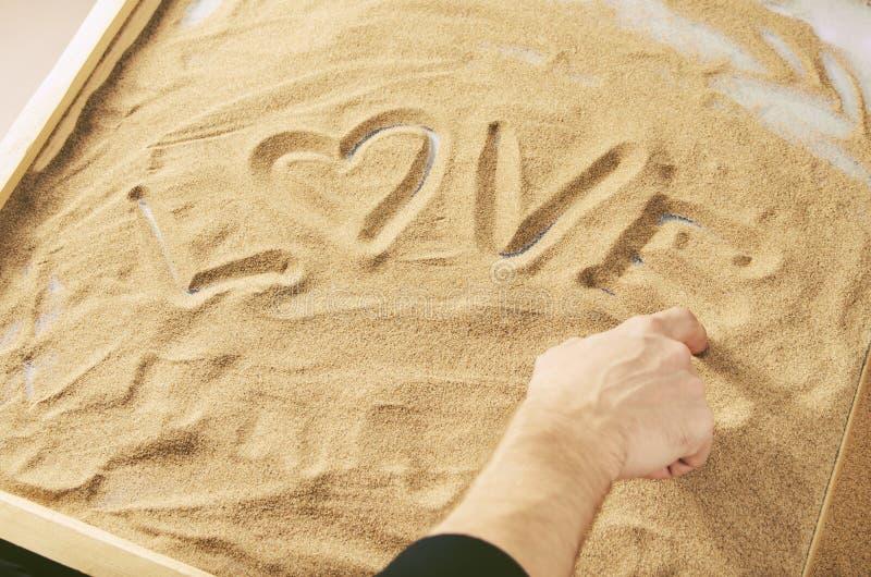 一个人由他的在沙子词爱的手指画与的心脏的标志 库存图片