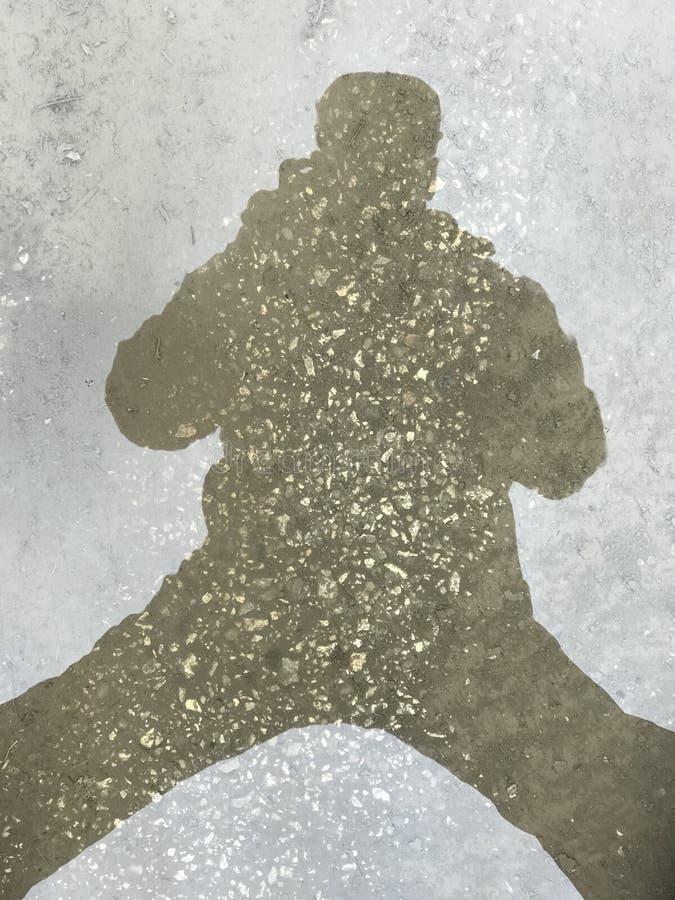 一个人的人阴影形象形状的好的特写镜头摘要视图在沥青表面,路背景的 库存照片