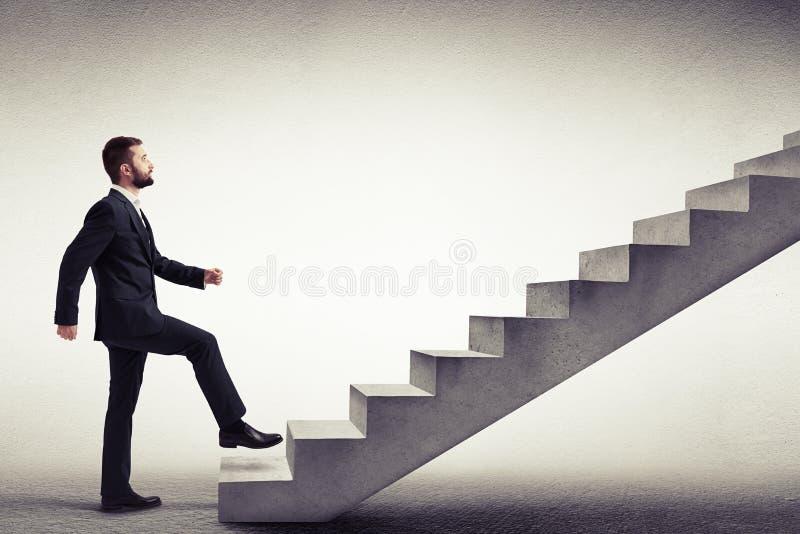 一个人的侧视图攀登具体台阶的一套礼服的 库存图片