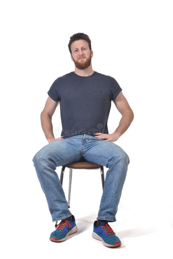 一个人的充分的画象坐在白色的一把椅子 库存图片