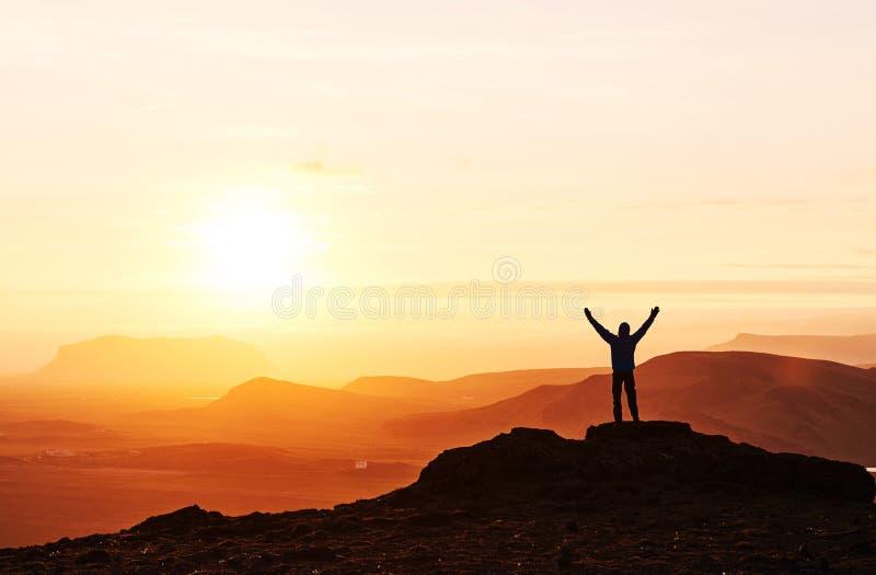 一个人的剪影在山上面的 在岩石的人剪影 体育和活跃生活概念 库存照片