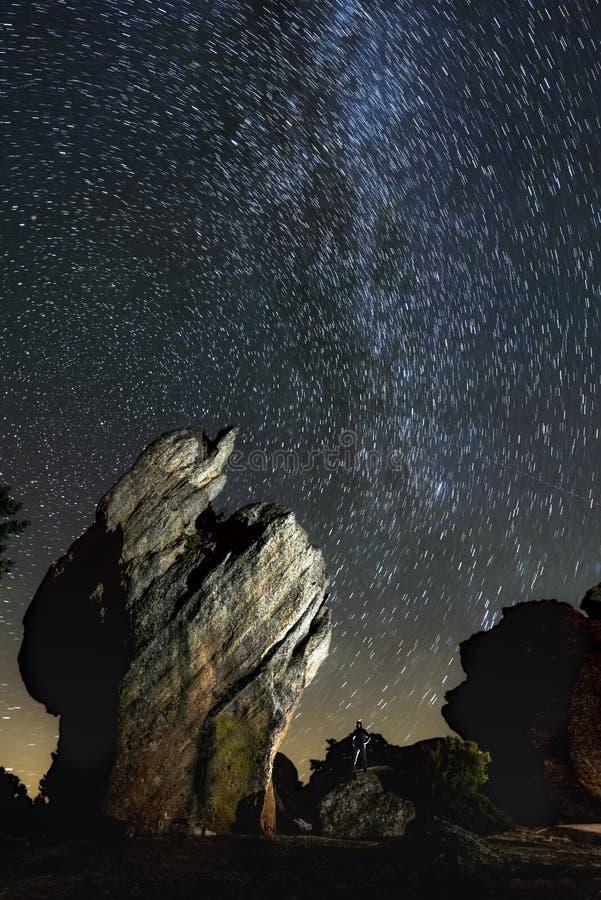 一个人的剪影在山顶部的夜与在惊人下的一个火炬银河 免版税图库摄影