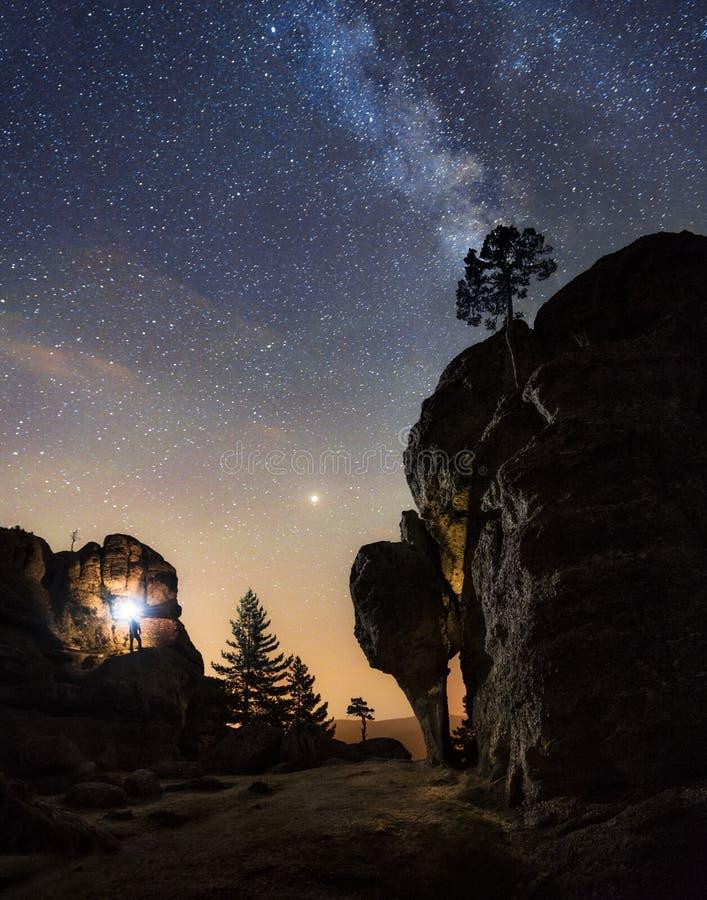 一个人的剪影在山顶部的夜与在惊人下的一个火炬银河 免版税库存照片