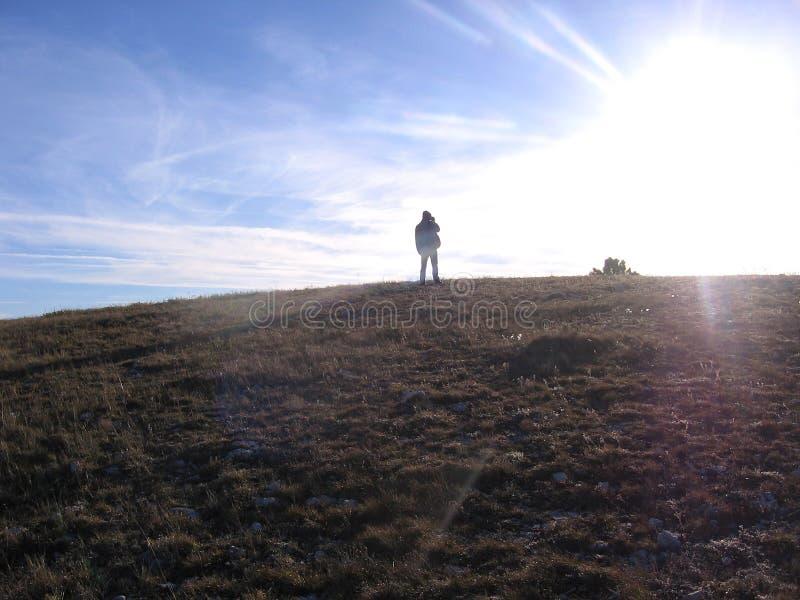 一个人的剪影在看太阳的小山顶部的 免版税库存照片