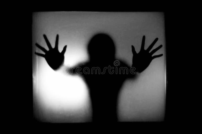 一个人的剪影在设法的玻璃后的逃脱在恐怖 免版税库存照片