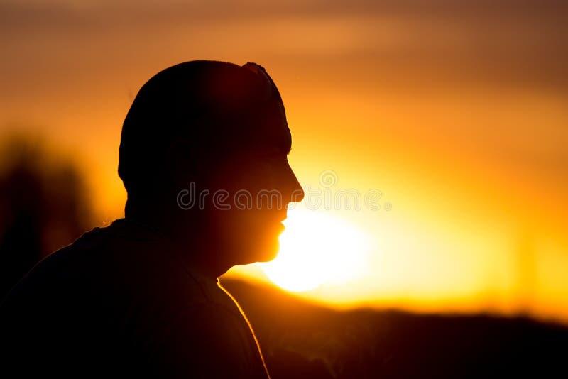 一个人的剪影戴眼镜的在日落 库存图片