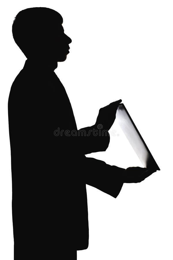 一个人的剪影有一个文件夹的在手上 图库摄影