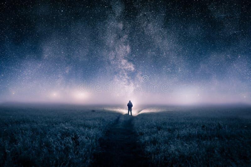 一个人的剪影有一个火炬的在领域,看在天际的光在喜怒无常的有薄雾的夜 星ove星系  库存照片