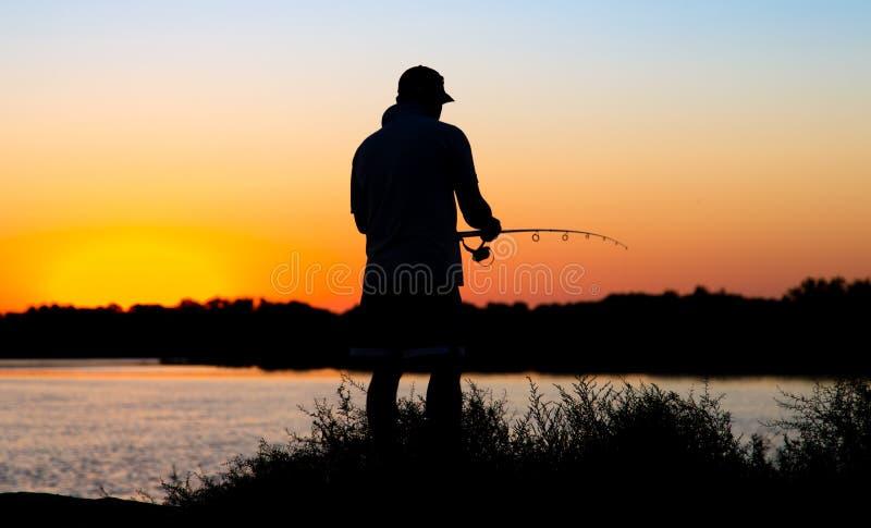 一个人的剪影有一根钓鱼竿的在日落 图库摄影