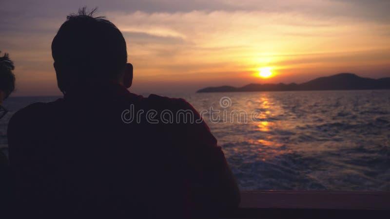 一个人的剪影船的 从海的看法到在日落,海景期间的海岛 库存图片