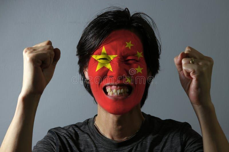 一个人的快乐的画象有中国的旗子的在他的在灰色背景的面孔绘了 体育或民族主义的概念 免版税库存照片
