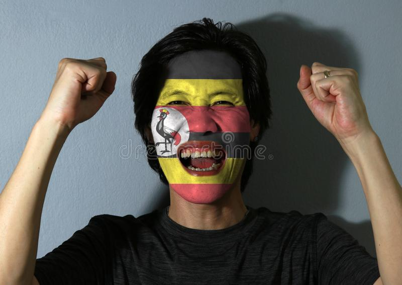 一个人的快乐的画象有乌干达的旗子的在他的在灰色背景的面孔绘了 体育或民族主义的概念 图库摄影