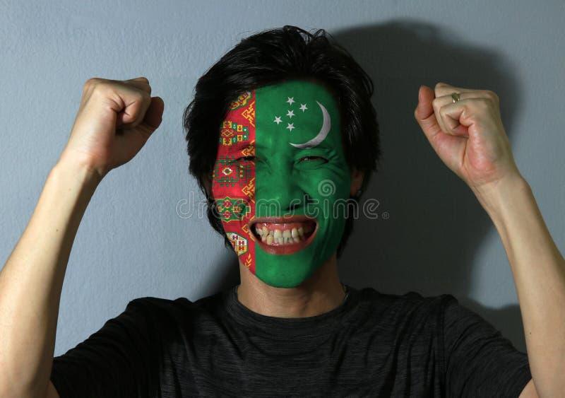 一个人的快乐的画象有土库曼斯坦旗子的在他的在灰色背景的面孔绘了 免版税库存图片