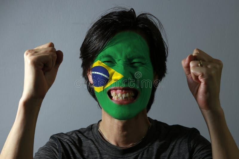 一个人的快乐的画象有巴西的旗子的在他的在灰色背景的面孔绘了 体育或民族主义的概念 免版税库存照片