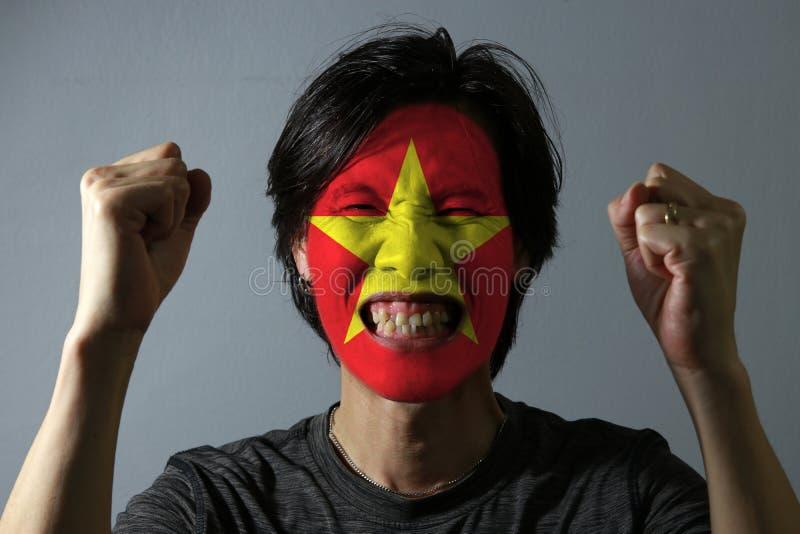一个人的快乐的画象有越南的旗子的在他的在灰色背景的面孔绘了 体育或nationalis的概念 免版税图库摄影