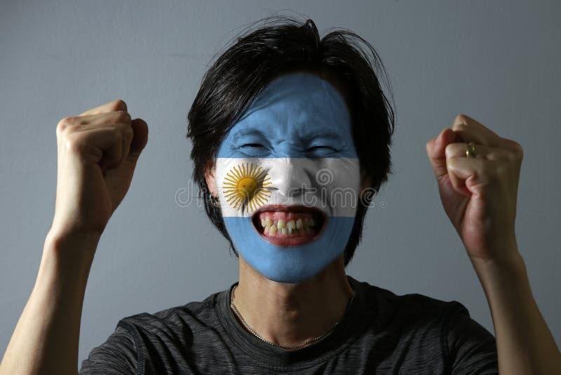 一个人的快乐的画象有阿根廷的旗子的在他的在灰色背景的面孔绘了 库存照片