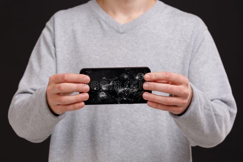 一个人的手一件灰色夹克的,拿着一个残破的智能手机 库存图片