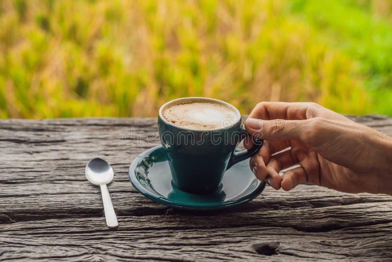 一个人的手拿着一杯咖啡在老木桌A心脏的背景的咖啡的 St华伦泰` s日 免版税库存图片