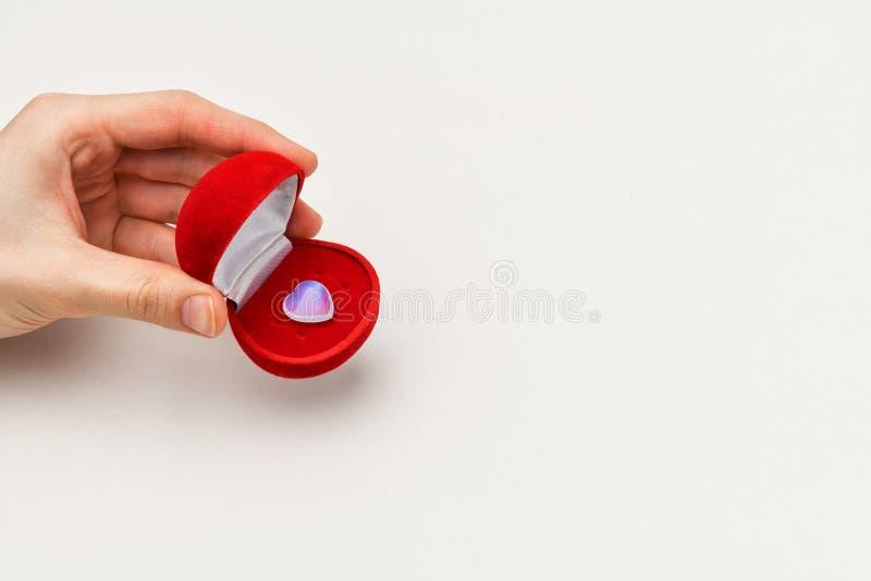 一个人的手的片段,有小透明心脏的一个红色首饰盒 免版税库存照片
