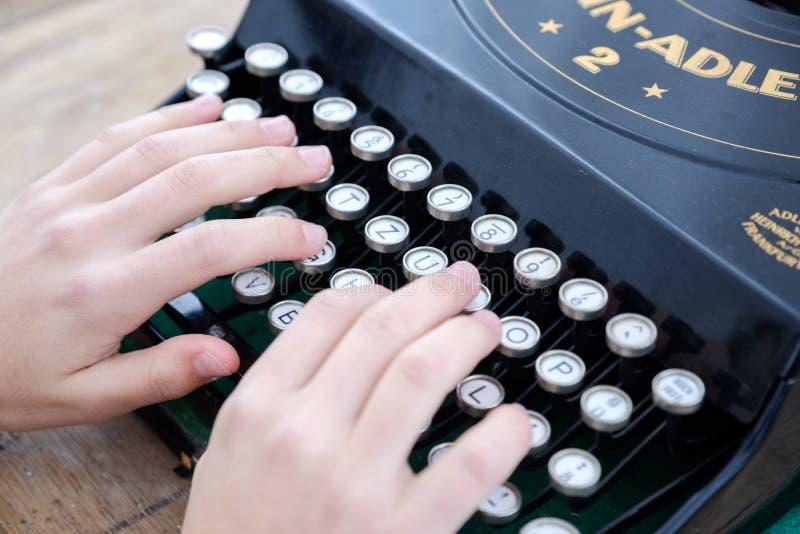 一个人的手的特写镜头键入在一台老打字机的 图库摄影