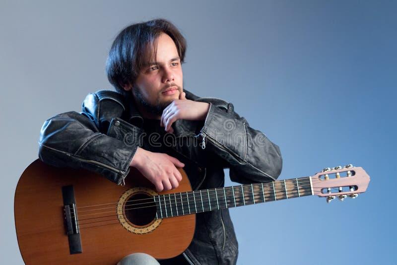 一个人的时髦的画象有一个胡子的在有一把声学吉他的一件黑夹克 背景看板卡祝贺邀请 音乐会或骑自行车的人 免版税库存照片