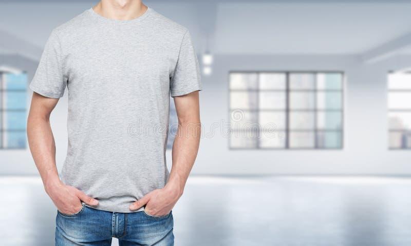 一个人的正面图一件浅灰色的T恤杉和牛仔布的 免版税库存照片