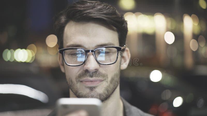 一个人的特写镜头有一个手机的在街道上的晚上 免版税库存图片